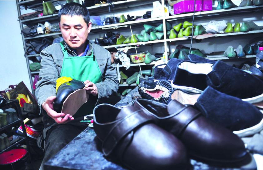 代俊士在将赶做好的56码鞋子打包装箱