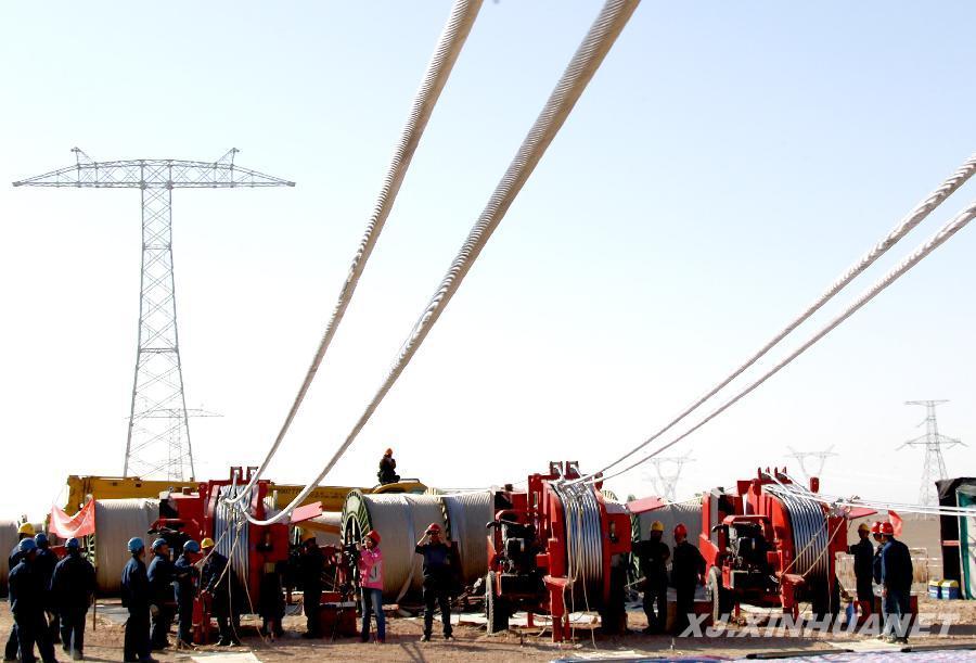 经过近一年的施工,新疆首条特高压输电线路哈密南至河南郑州800千伏特高压直流输电工程塔架施工近日接近尾声,输电线路全线开架,预计在2014年建成投运。这条特高压直流线路途经新疆、甘肃、宁夏、陕西、山西、河南六省(区),全长2210公里,总投资233.9亿元,建成后输电能力将达800万千瓦。  3月27日,电力建设者在新疆哈密南至河南郑州800千伏特高压直流输电工程工地上牵引导线。  3月27日,新疆哈密南至河南郑州800千伏特高压直流输电工程新疆段输电线路首放成功。  3月27日,新疆哈密南至河南郑